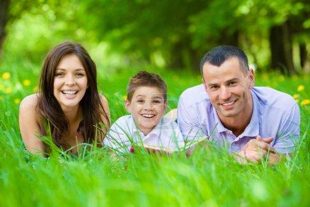 Dreiköpfige glückliche Familie liegt mit Buch im Gras