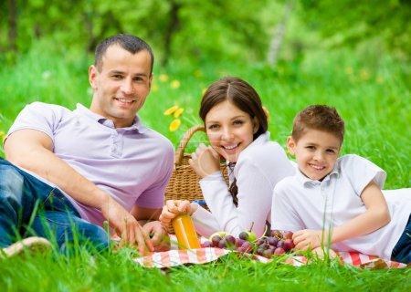 Happy family of three has picnic in park