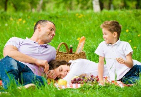Dreiköpfige Familie picknickt im grünen Park