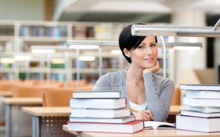 Photo pour Des étudiantes souriantes avec des tas de livres assis à la bibliothèque - image libre de droit