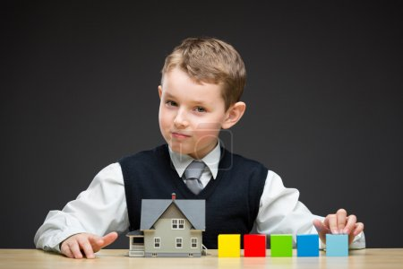 Little boy with house model and blocks