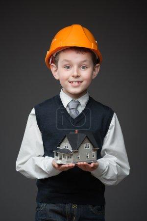 Boy in hard hat keeping house model