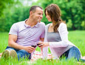 Pretty couple drinks wine in park