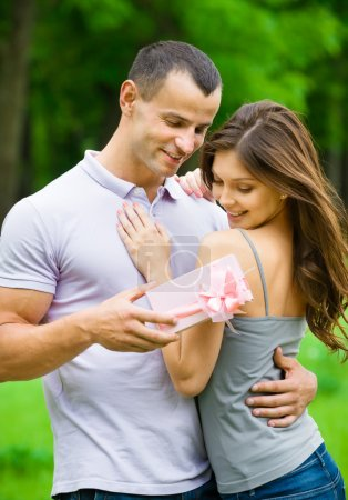 Man gives present to woman in park