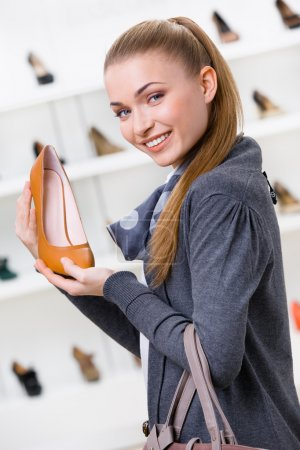 Woman keeping brown leather shoe