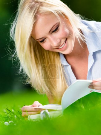 Pretty girl reading book on the grass