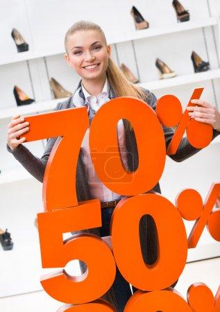 Photo pour Femme montrant le pourcentage des ventes de chaussures à talons hauts dans le centre commercial contre le boîtier de fenêtre avec des pompes - image libre de droit
