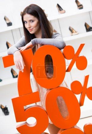 Photo pour Femme montrant le pourcentage des ventes de chaussures élégantes dans le centre commercial contre le boîtier de fenêtre avec des pompes - image libre de droit