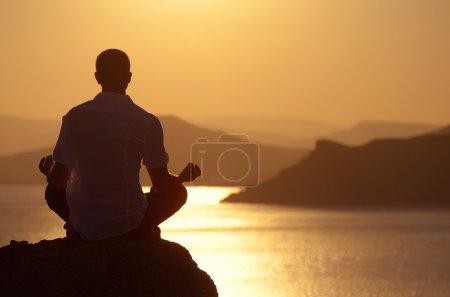 Photo pour Guy méditant au coucher du soleil assis sur un rocher au bord de la mer - image libre de droit