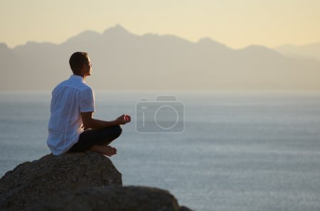 Guy sitting on a rock in the lotus position