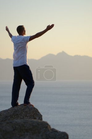 Man stands on a rock by the sea with his arms raised to the sky