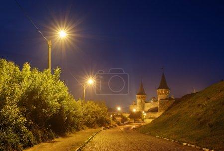 Photo pour Paysage nocturne avec une route menant à l'ancienne forteresse. Lampe dans la rue. Repère historique. Vieille ville de Kamenetz-Podolsk, Ukraine, Europe - image libre de droit