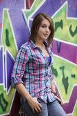 Style teen girl standing near graffiti wall.