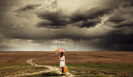 Girl with umbrella and suitcase walking by the road at countrysi
