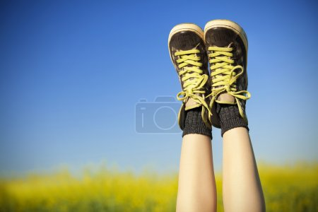 vintage sneakers resting on blue sky and rapseed field backgroun