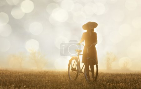 Girl and on a bike in the countryside in sunrise time