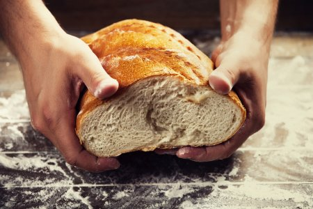 Baker's hands with a bread