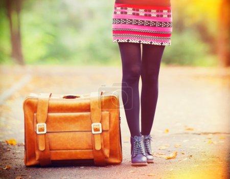 Women's foots near suitcase at autumn outdoor
