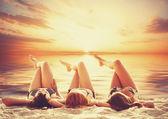 trois filles sur la plage au coucher du soleil