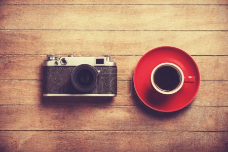 Retro camera and cup of a coffee.
