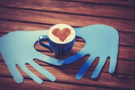 Cup of coffee with heart shape and paper hands.