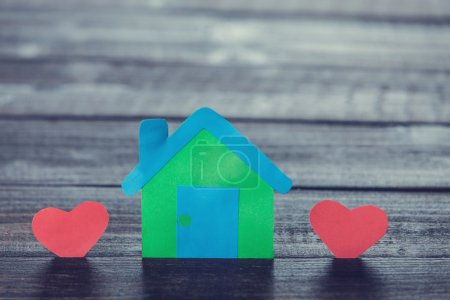 Paper house and shape hearts on wooden table.
