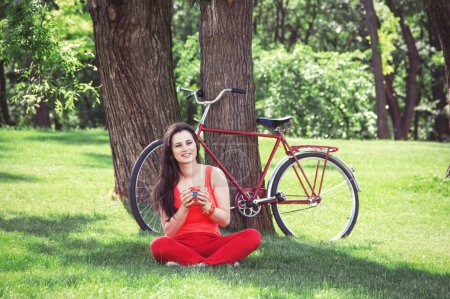 Brunette girl with cup of coffee in the park and with bicycle on