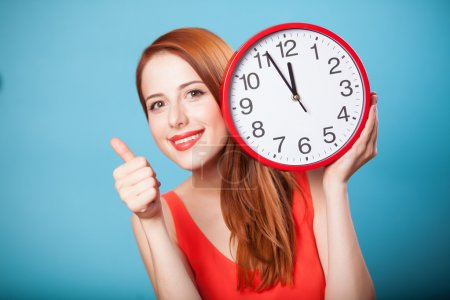 Redhead girl with huge clock on blue background.