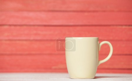 Tea or coffee cup on wooden table.