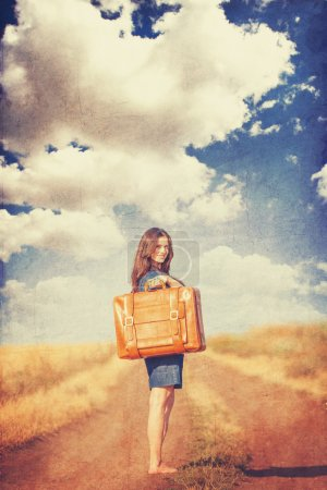 Brunette girl with suitcase on countryside road.