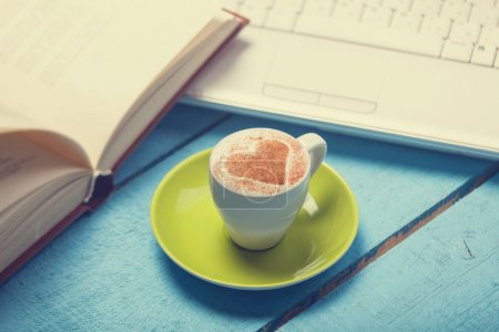 Cup of coffe with laptop and book on blue wooden table.