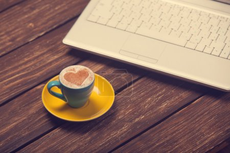 Cup of coffee with heart shape and notebook on wooden table.