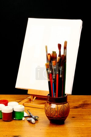 Photo for Canvas,brushes and easel in black background - Royalty Free Image