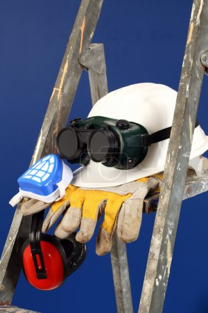 Photo for Safety gear kit on step ladder over blue - Royalty Free Image