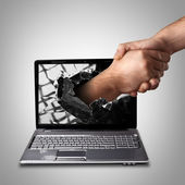 A hand comes right out of the laptop screen to shake hands