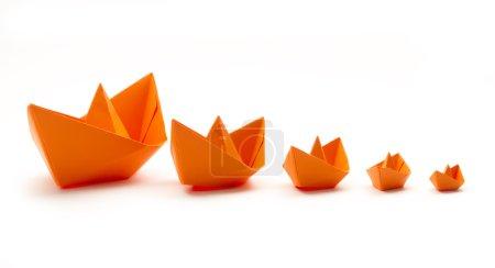 Foto de Barcos de origami de papel naranja en fila aislado - Imagen libre de derechos