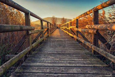 Photo pour Petit pont en bois sur le lac au coucher du soleil - image libre de droit