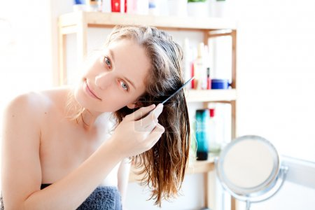 Young girl taking care of her hairs in a bathroom