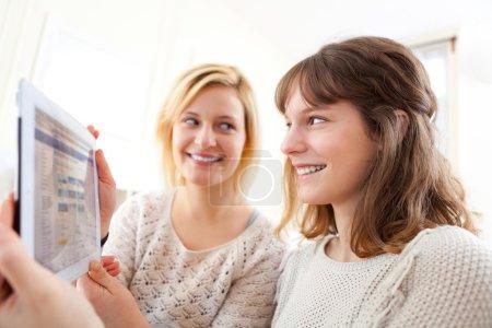 Girls choosing their holidays destination on tablet