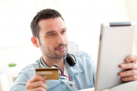 Young relaxed man buying music on tablet