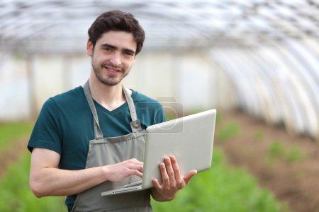 Photo pour Vue d'un jeune agriculteur travaillant sur son ordinateur portable - image libre de droit