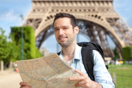 Young attractive tourist reading map in Paris