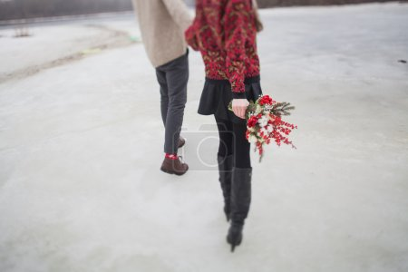 Woman and man in the park in winter with a bouquet...
