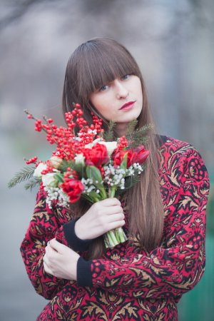 Photo for Beautiful girl in the park in winter,  with a bouquet of red flowers - Royalty Free Image