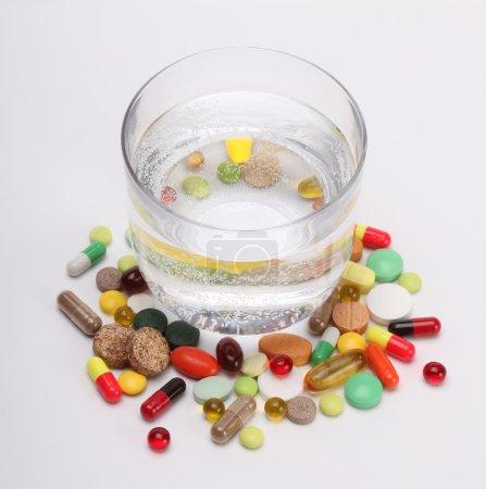 Photo pour Vitamines, comprimés et pilules et verre d'eau - image libre de droit