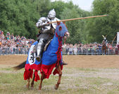 Knight in heavy armor on a horse and with a lance