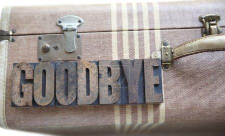 Photo pour Les adieux de mot en vieux type bois de typographie sur une vieille valise - image libre de droit