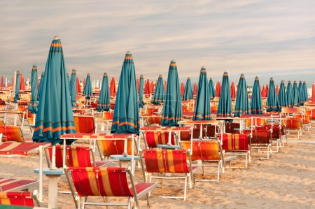 Withdrawn umbrellas and sunlongers on the sandy beach in Italy