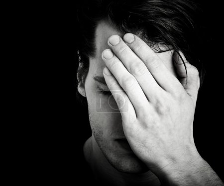 Photo for Sad young man with hands before face and dark background - Royalty Free Image