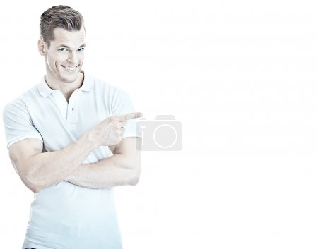 Handsome and sportive young man pointing at empty copyspace